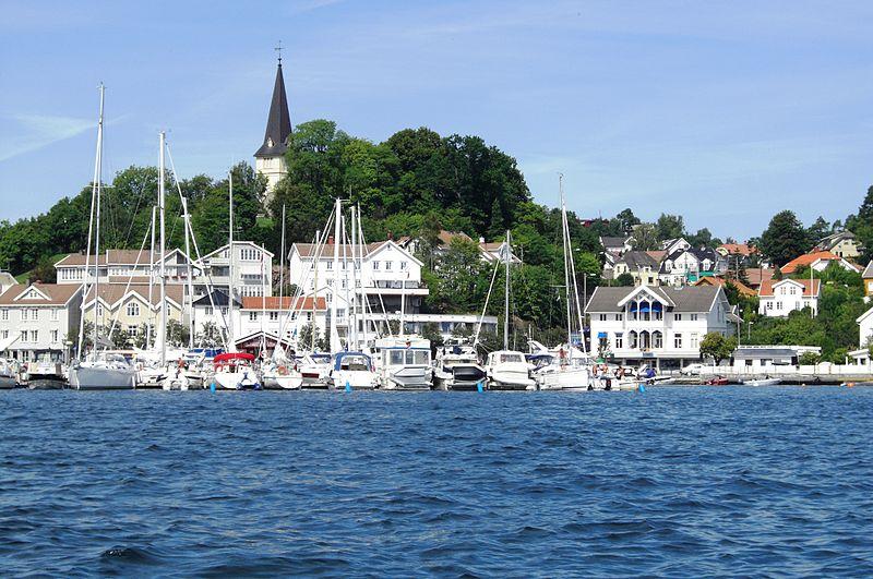 Grimstad by sett fra sjøsiden med kirken i bakgrunnen. Masse båter på havna.