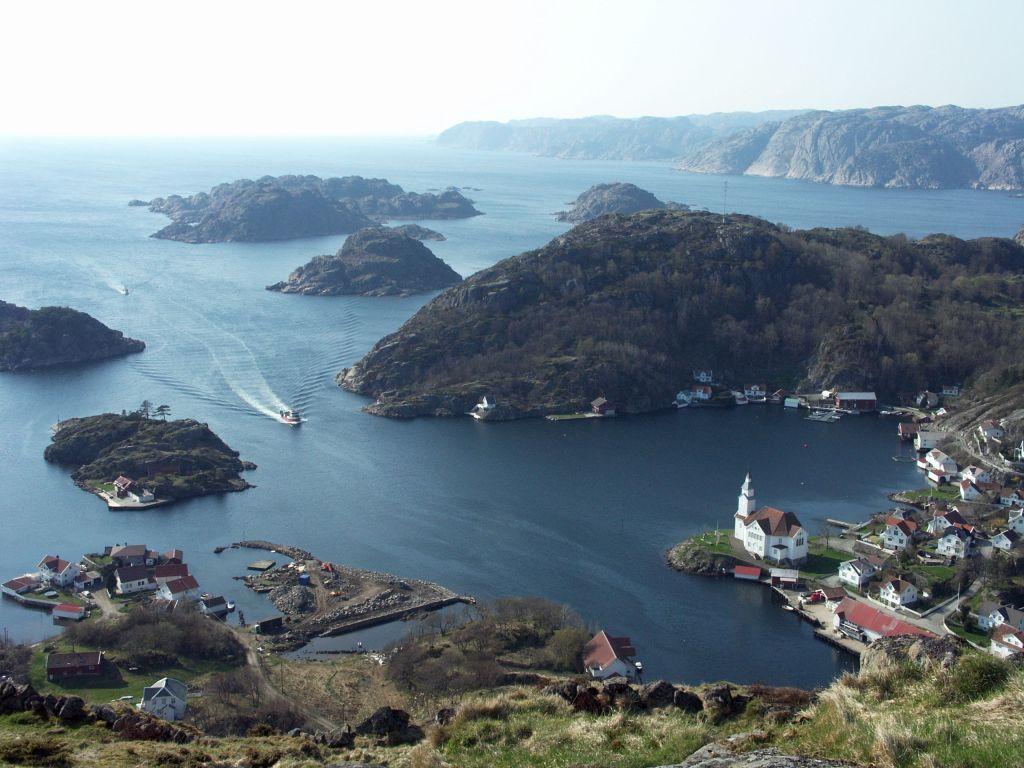 Tettstedet Kirkehavn på Hidra sett fra toppen av Hågåsen. Flott skjærgård med båt på vei inn.
