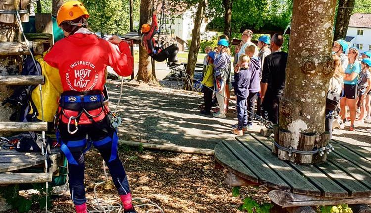 Mange barn med hjelm på besøk i klatrepark. Får instrukser før de kan begynne klatringen.