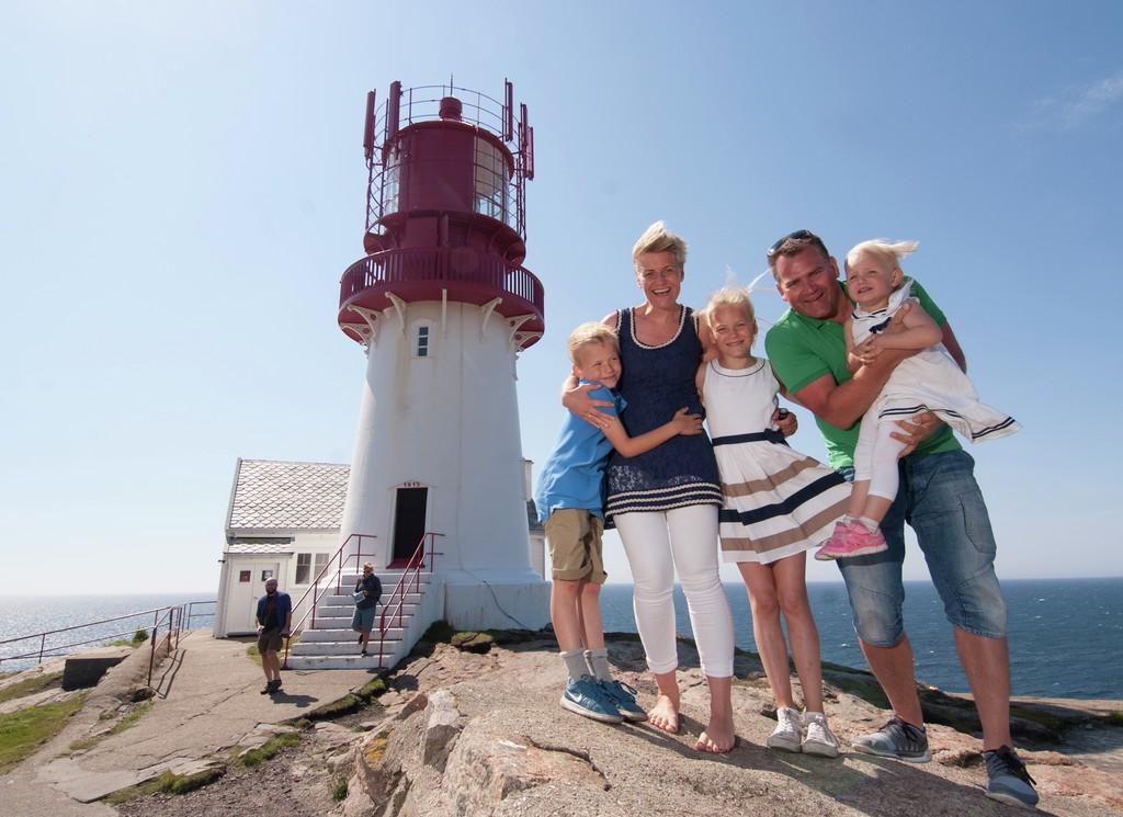 Familie med far og mor og tre mindre barn poserer glade og smilende foran Lindesnes fyr.