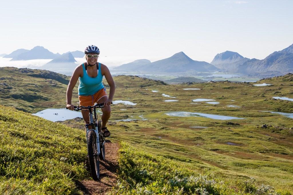 Dame med hjelm sykler på sti i fjellet i Lofoten. Vestvågøy.