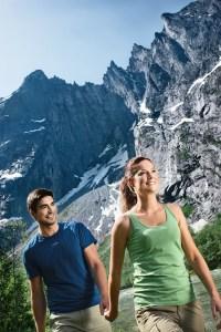 Yngre par på vandretur langs elva Rauma med Trollveggen i bakgrunnen.