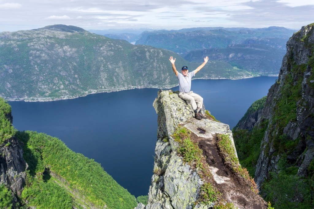 Voksen mann strekker armene i været mens han sitter på en fjellformasjon. Jøsenfjorden ses i bakrunnen.