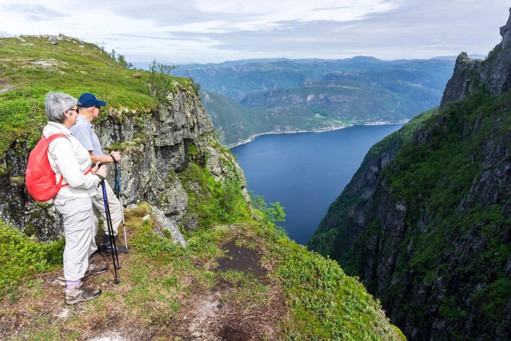 Et voksent ektepar med gåstaver nyter en fantastisk utsikt over Jøsenfjorden.