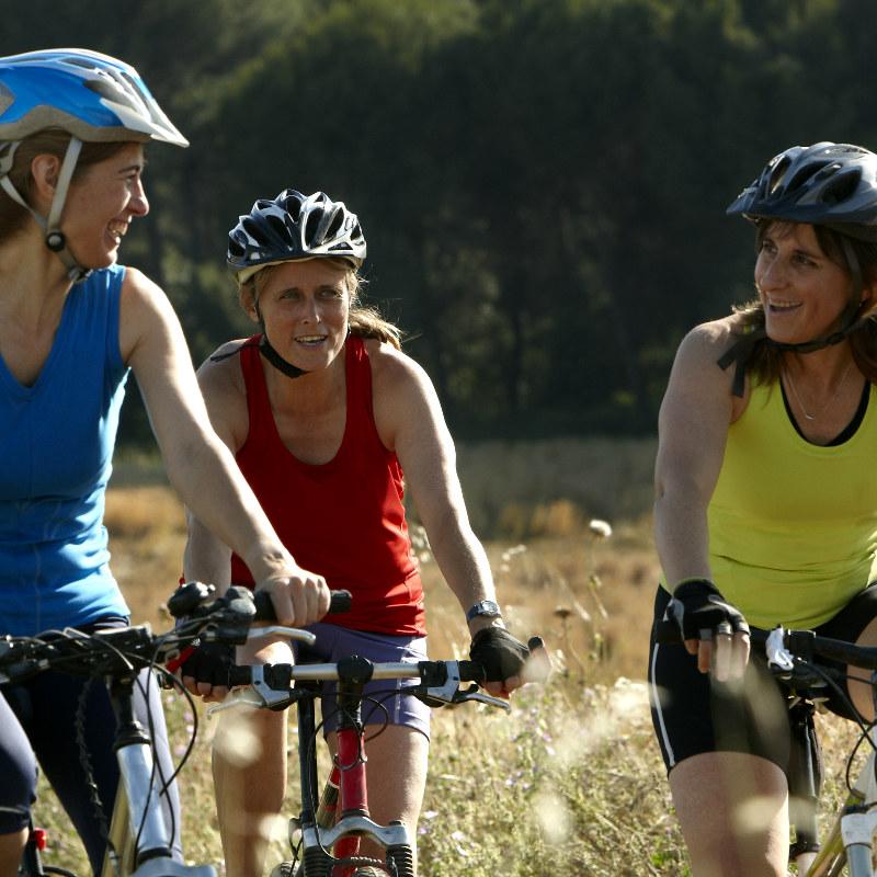 Tre damer med hjelp på sykkeltur i Numedal.