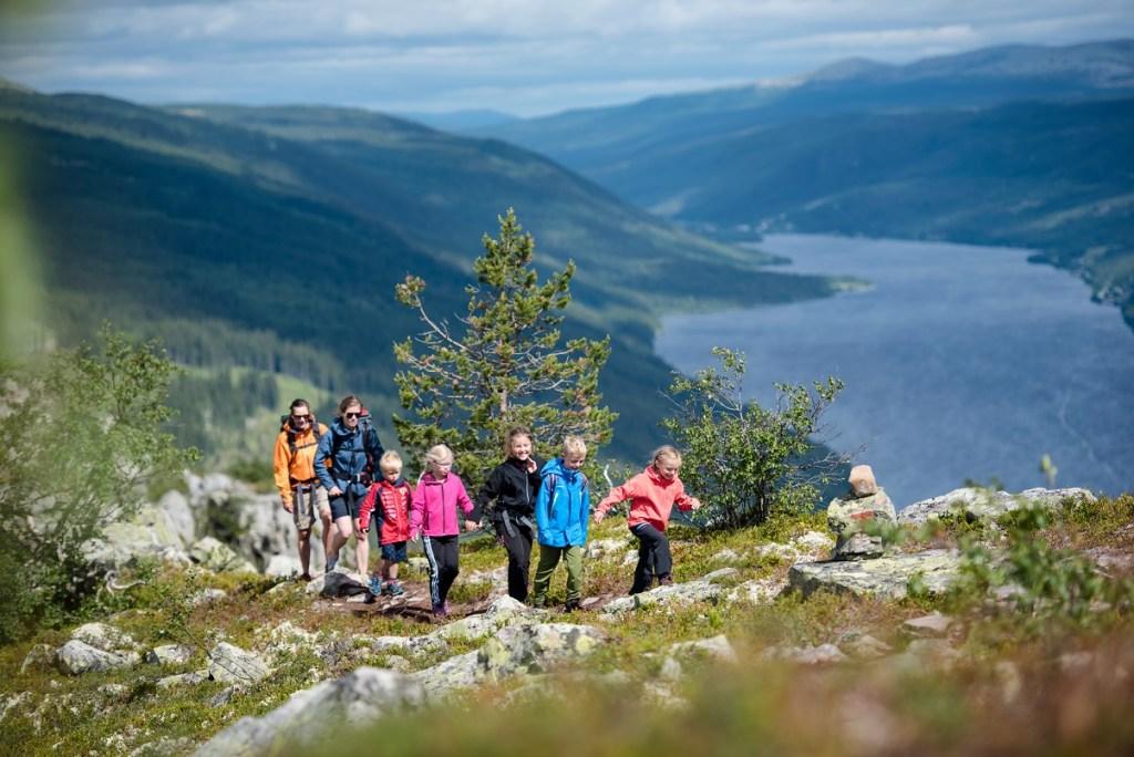 Familie med to voksne og fem barn på god vei opp til Skagsvola i Trysil med Engersjøen i bakgrunnen.