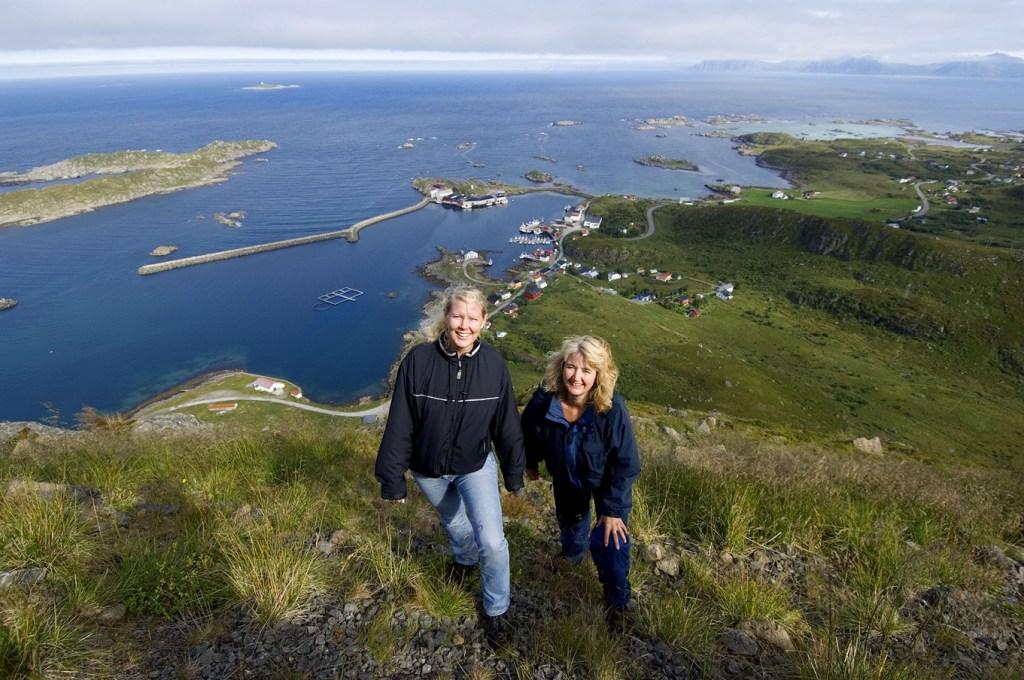 To jenter på fjellet med fiskeværet Stø i bakgrunnen.