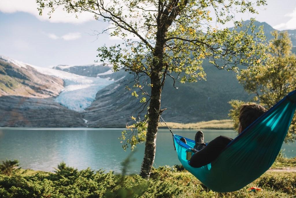 Mann ligger i hengekøye med utsikt til Engabreen i Svartisen.