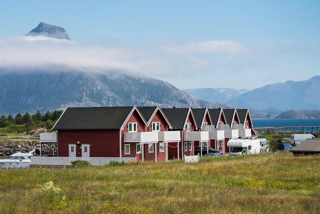 Rødmalte rorbuer på Bolga Brygge med fjell i bakgrunnen.