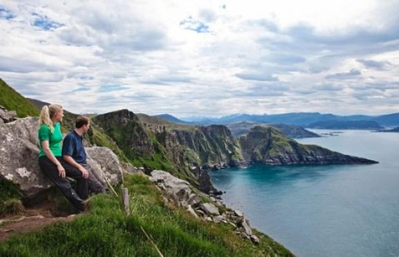 Par sitter og nyter utsikten over øya Runde på Sunnmøre.