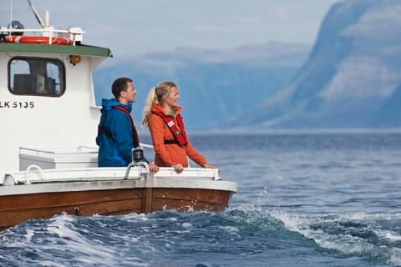 Mann og damen står akter i en sightseeingbåt på vei rundt øya Runde på Sunnmøre.