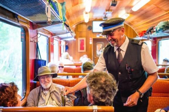En blid konduktør sjekker billetter til turister på Flåmsbana.