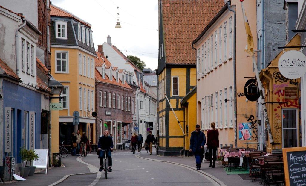 Bystemning fra Århus i Danmark. Mann på sykkel kommer mot oss. Folk i spaserer i gatene.