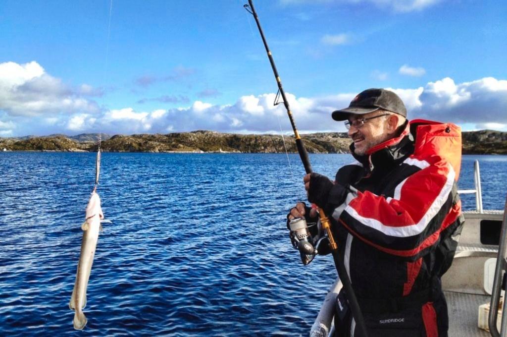 Mann med fiskestang lander en fin fisk fra båt.