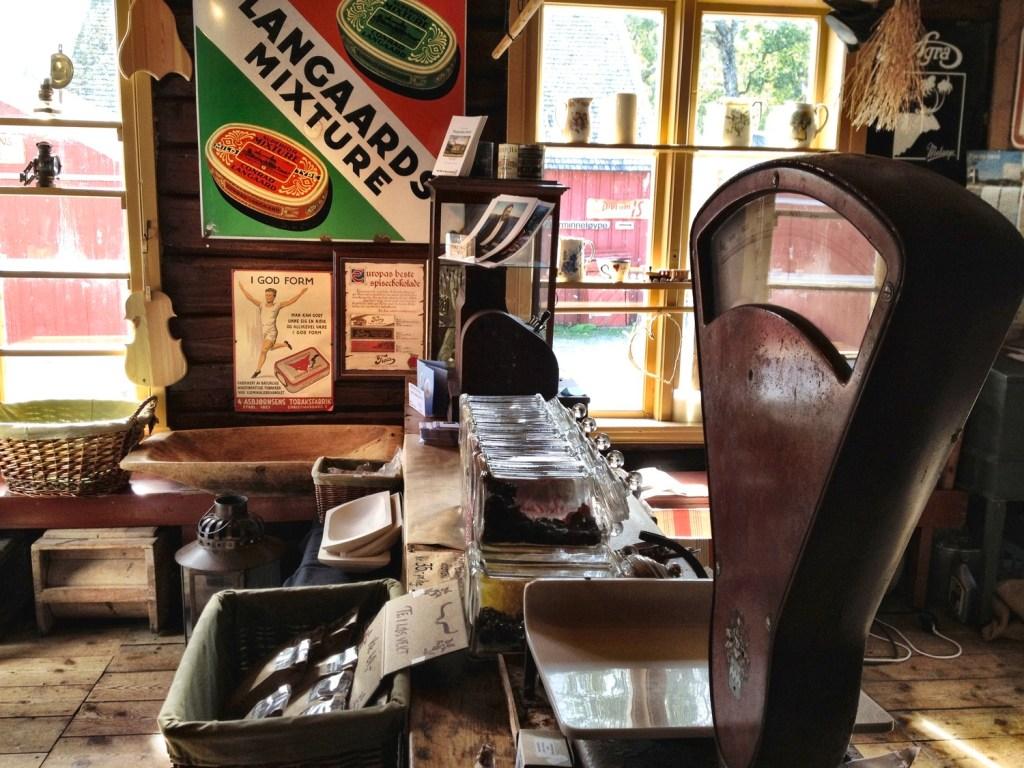 Interiør fra en gammel landhandel med tobakksreklame på veggen og en gammel vekt på disken.