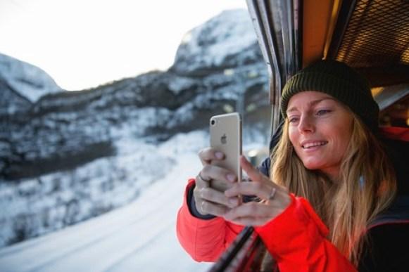 Ung dame med grønn lue tar bilde med mobil ut av togvindu på Flåmsbana vinterstid.