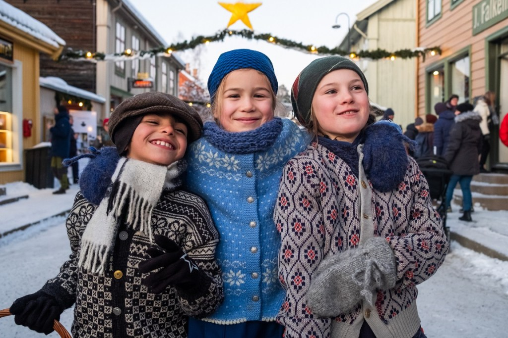 Tre glade barn på julemarked på Maihaugen. Kledd i strikkejakker og votter. Julegatebelysning i bakgrunnen.