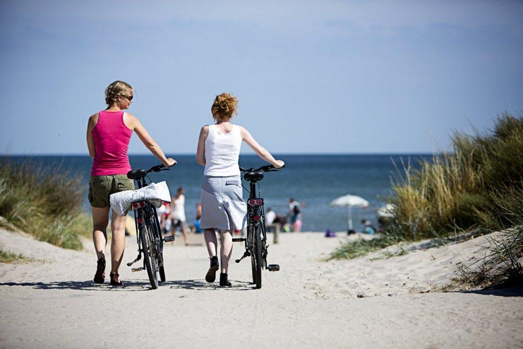 To damer triller hver sin sykkel på en hvit sandstrand med utsikt mot havet.