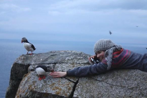 Ung jente ligger på fjellet og har nærkontakt med lundefugl. Har kamera og håper på blinkskudd.
