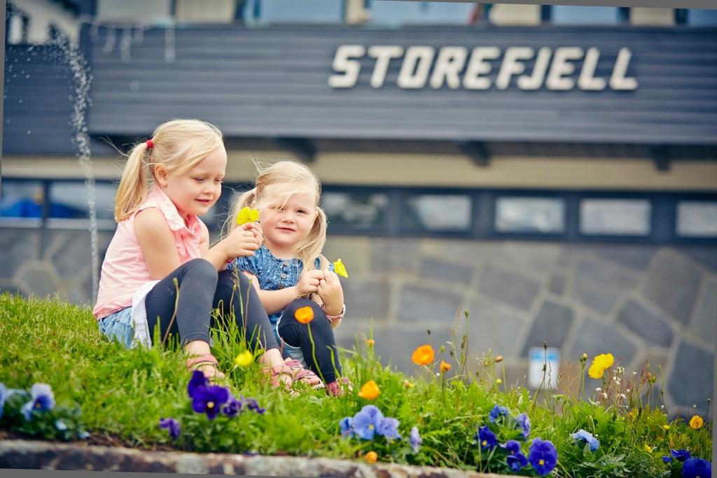 To unge jenter plukker blomster foran Storefjell Resort Hotel på Golsfjellet.