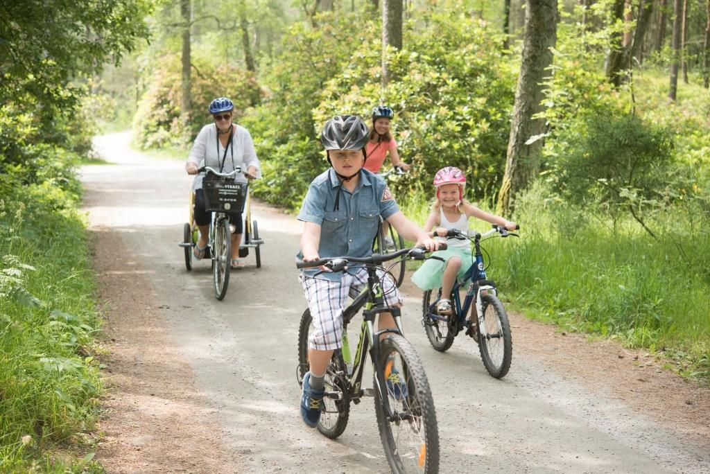 Familie med mor og tre barn på sykkeltur i Furulunden i Mandal.