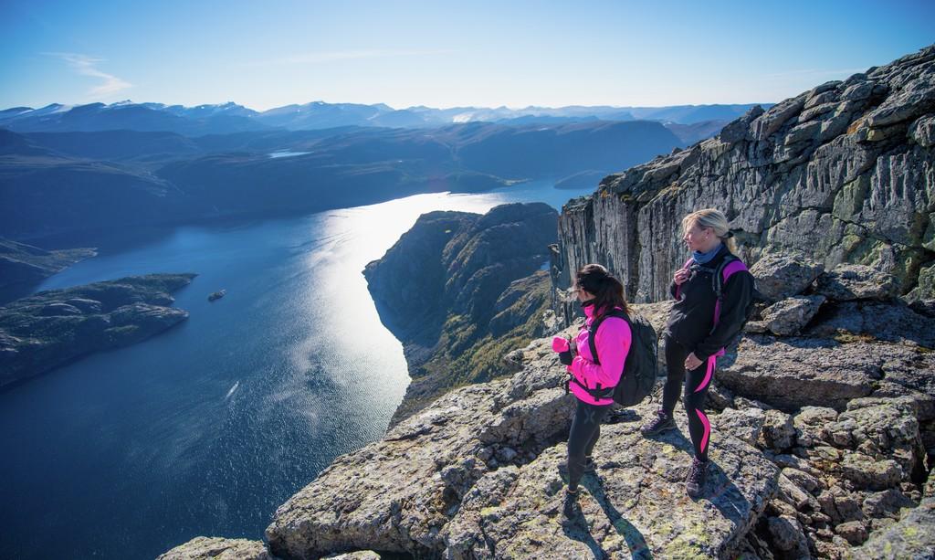 To turkledde damer har tatt seg til topps på Hornelen i Bremanger og nyter utsikten ned mot fjorden. Dette er Europas høyeste havklippe.