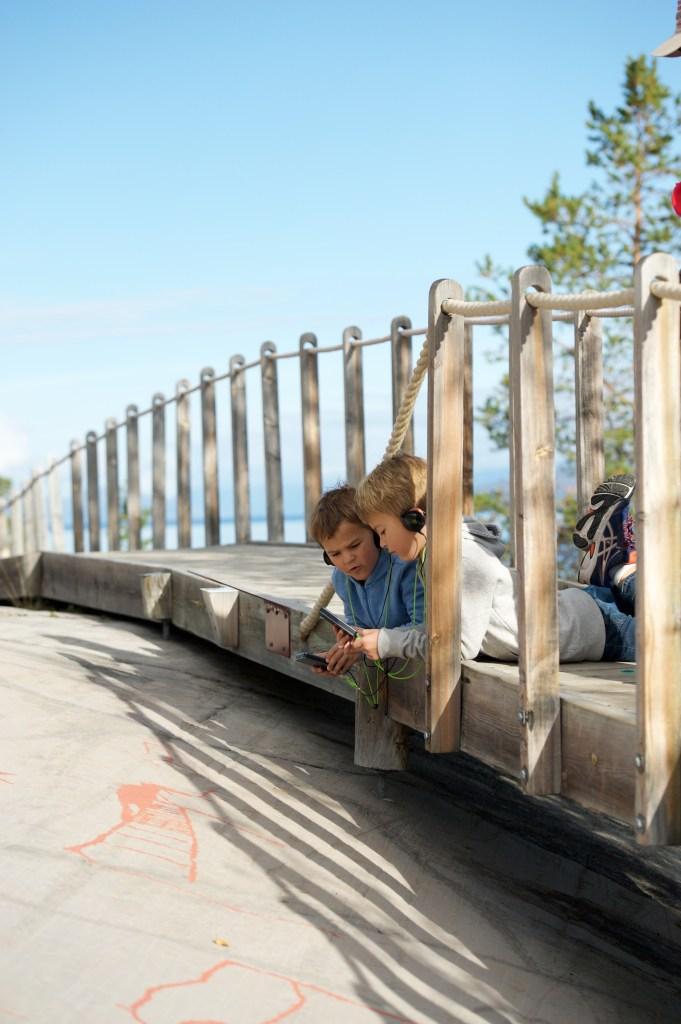 To gutter beundrer helleristninger på Alta Museum mens de hører på digital guidebok.