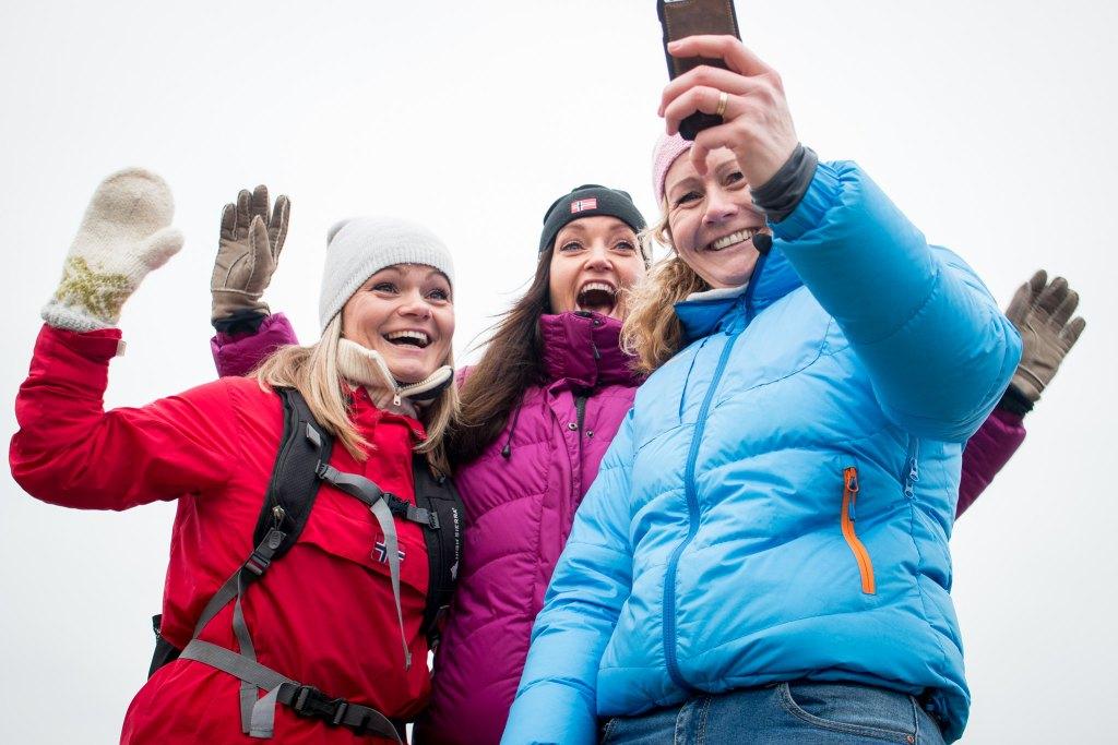 Tre unge damer tar en selfie mens de går kyststien i Stavern.