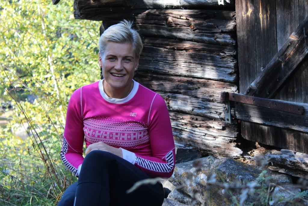 Voksen dame i rosa genser sitter på trappa til en gammel tømmerkoie. Hovden i Setesdal.