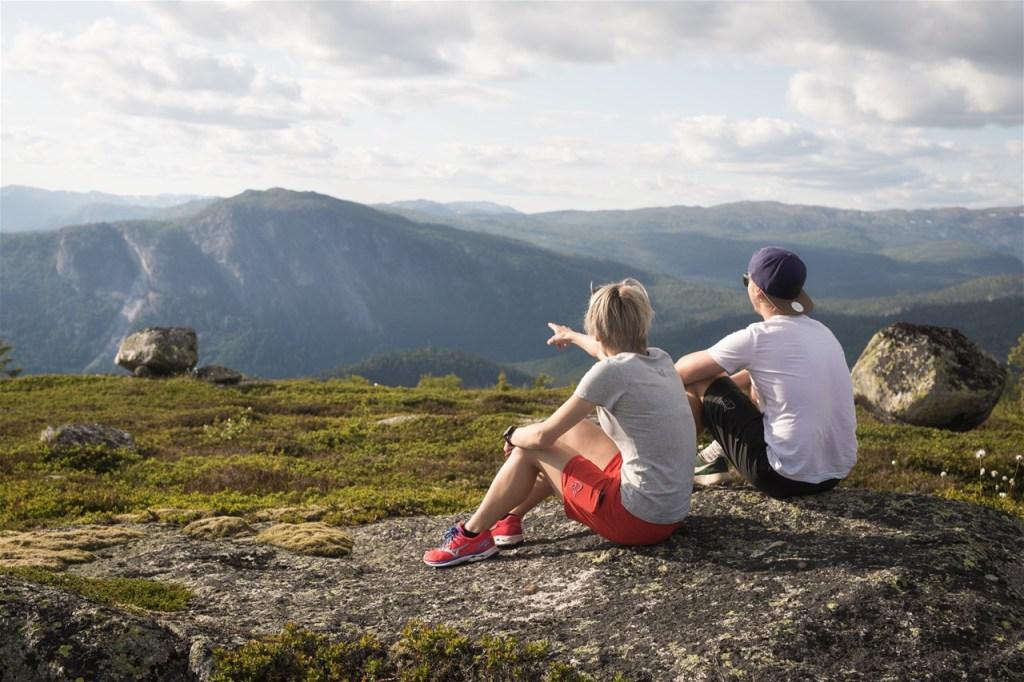 To jenter sitter på fjellet på Hovden i Setesdal og nyter utsikten. Lett kledde i shorts og t-skjorter.