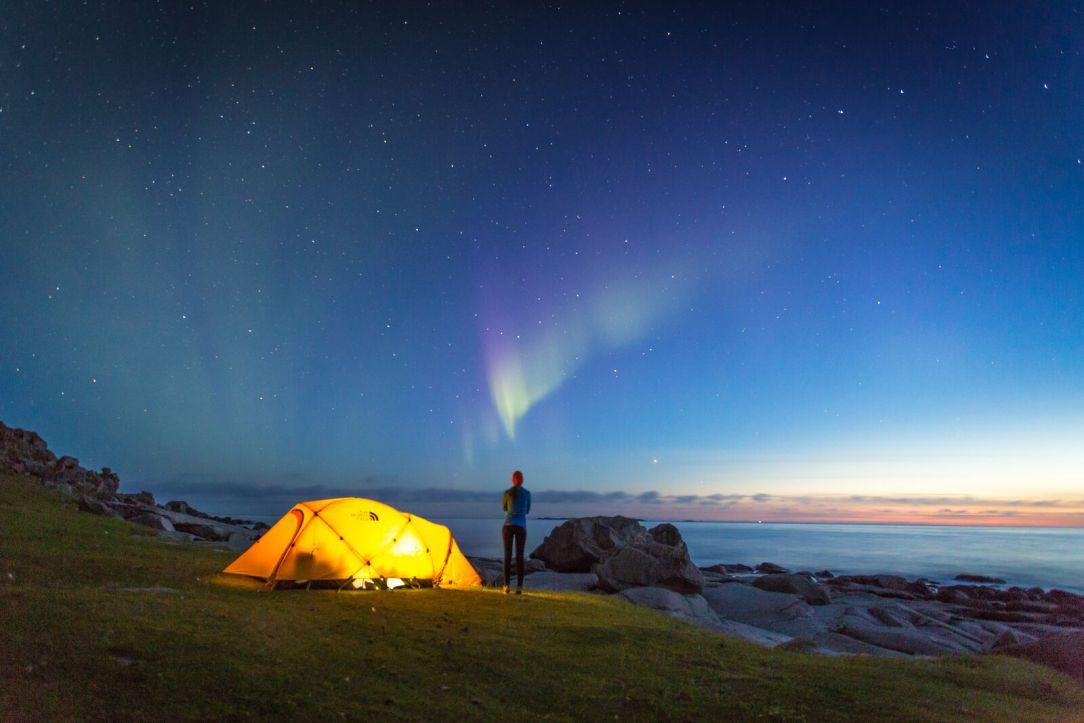 Telt person blå nattehimmel med nordlys