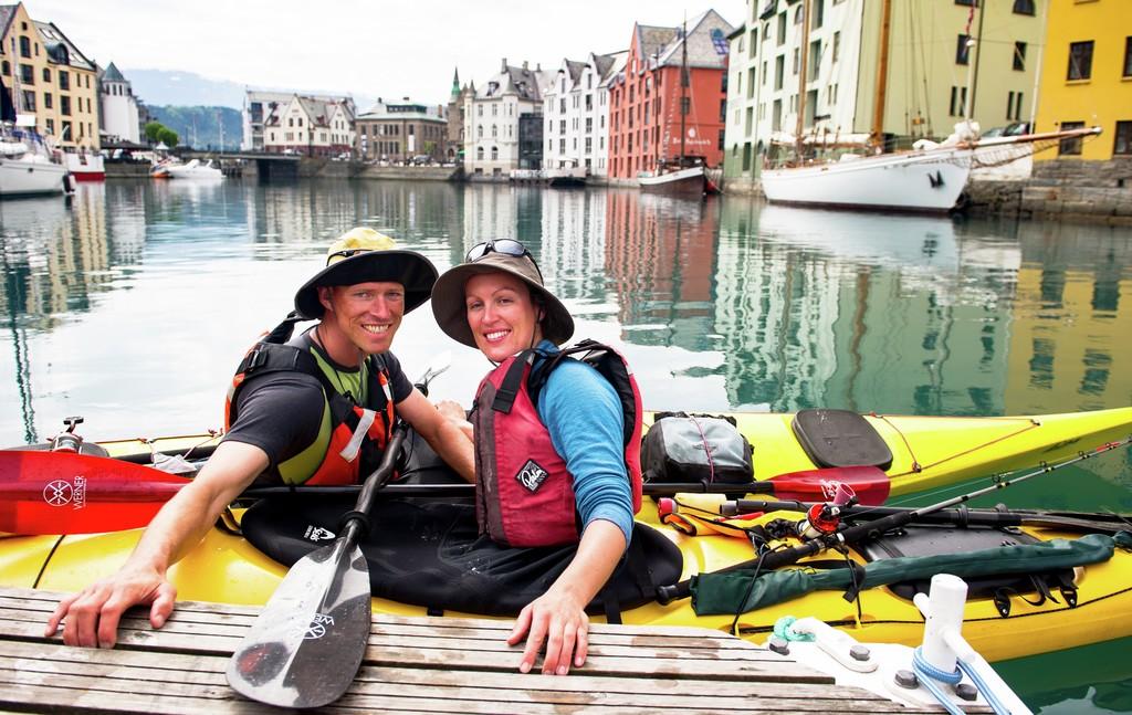 Par med solhatter padler kano i Ålesund