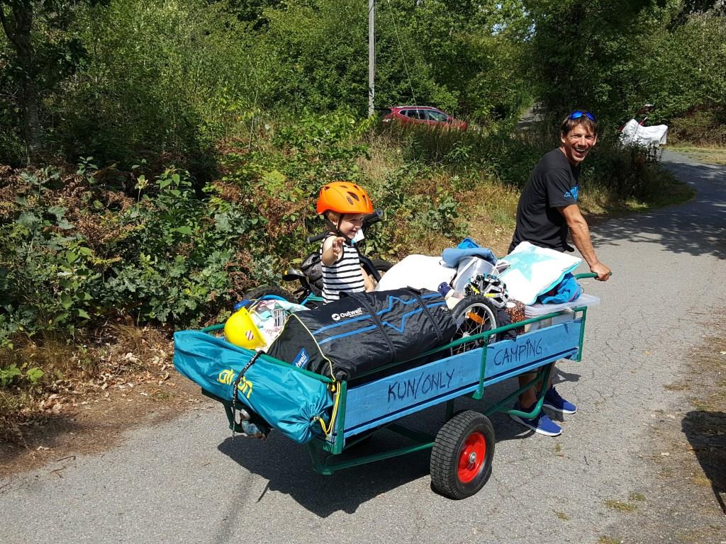 Mann trekker kjerre med barn sykkel og utstyr Ula telt