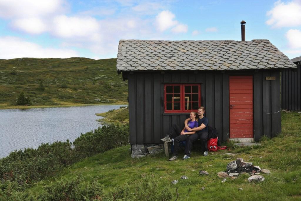 Ungt par på tur sitter i hytteveggen