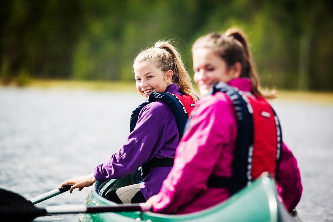 Blide jenter padler kano på Fjorda