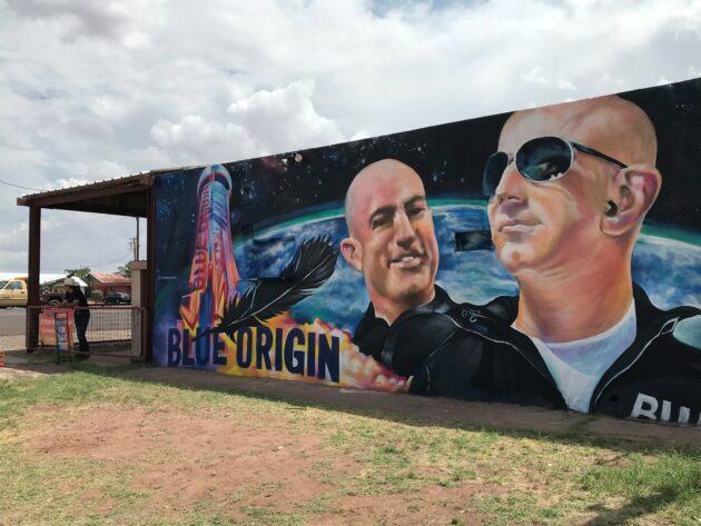 De ruimteopnamen van Blue Origin geven het kleine stadje in Texas een boost die groter is dan verwacht  Een muurschildering geschilderd op een gebouw dat te koop staat in Van Horn, Texas, toont Jeff Bezos en zijn broer Mark, die dinsdag in het suborbitale ruimteschip van Blue Origin zullen rijden. (GeekWire-foto / Alan Boyle) VAN HORN, Texas — Toen ik deze stad in West-Texas voor het laatst in 2006 bezocht, was de ruimtevaartonderneming Blue Origin van Jeff Bezos van plan om tegen 2010 suborbitale ruimtereizen aan te bieden voor betalende passagiers . Het slechte nieuws voor Van Horn is dat het tien jaar langer heeft geduurd dan verwacht voordat de ruimtevaart van Blue Origin naar Van Horn kwam. Maar het goede nieuws is dat de economische impact aantoonbaar tien keer zo groot is. De 15 jaar oude milieubeoordeling van Blue Origin, die het onderwerp was van de hoorzitting van de Federal Aviation Administration die ik in 2006 bijwoonde, schatte dat 20 tot 35 voltijdse werknemers zouden werken op de suborbitale lanceerbasis van het bedrijf, een halfuur rijden ten noorden van Van Hoorn. Vijftien jaar later is het werkelijke aantal 275 werknemers – niet alleen vanwege het suborbital-ruimteschip New Shepard van Blue Origin, dat Bezos en drie bemanningsleden dinsdag zullen besturen, maar ook vanwege het testprogramma voor raketmotoren dat is gebaseerd op Launch Site One. De BE-3-motoren die op New Shepard worden gebruikt, worden gebouwd in het hoofdkantoor van Blue Origin in Kent, Washington, maar worden in Texas tot in de puntjes uitgeprobeerd. Launch Site One is ook de testsite voor de krachtigere BE-4-raketmotoren van Blue Origin.  Patricia Golden, directeur van Van Horn's Clark Hotel Museum, pronkt met een schaalmodel van Blue Origin's New Shepard suborbital raketschip. (GeekWire-foto / Alan Boyle) Het personeelsbestand van Blue Origin in West-Texas vormt slechts een fractie van het totale personeelsbestand van Blue Origin van meer dan 3.500 mensen. Niettemin hebben 275