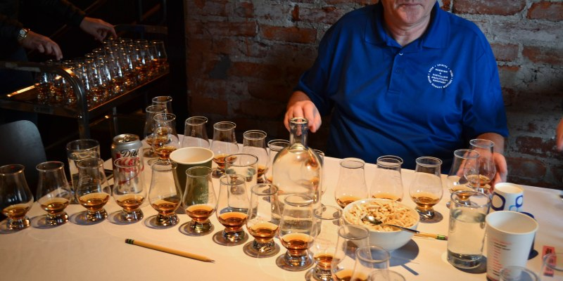 Man sitting in front of whiskey in shot glasses, waiting to sample
