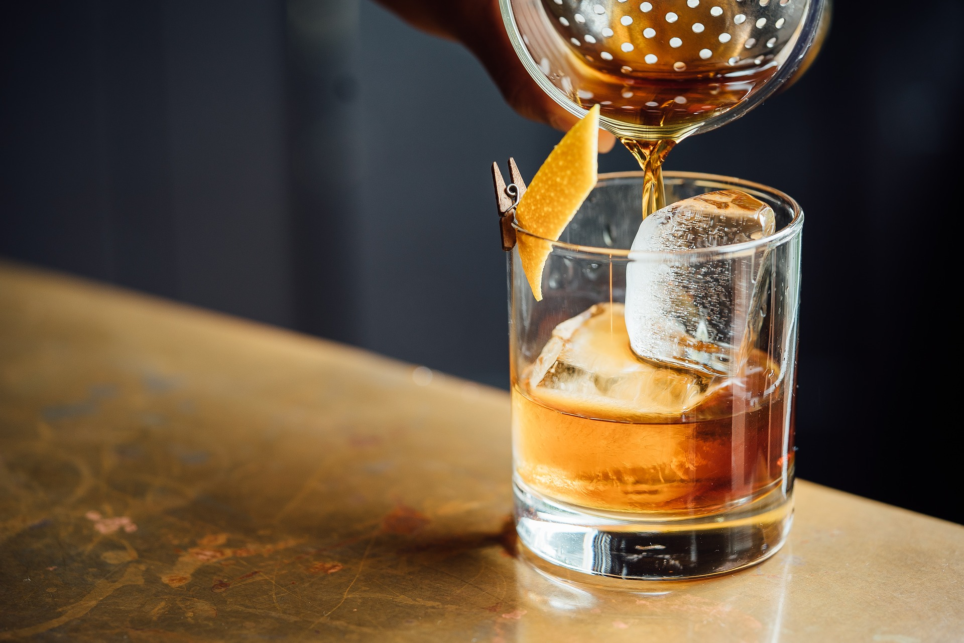 whiskey being poured into a glass through cocktail strainer