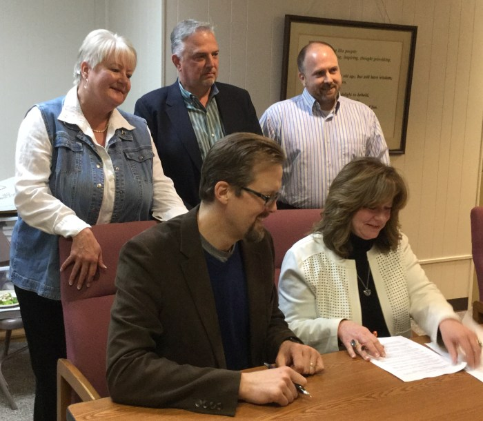 Our Daily Bread Board President Andrew Ranson and Mayor Gina Noble sign the lease for the space where Our Daily Bread will soon open. Behind them are Kathy Sandefur, ODB Vice President, John Dorman, City Attorney, and Rod Goodner, ODB Treasurer