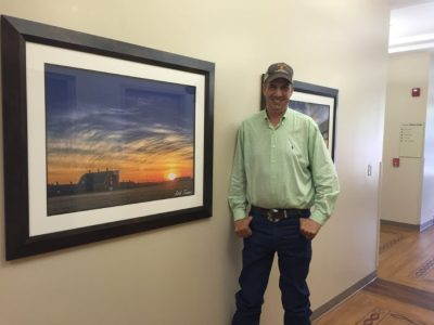Kirk Turner stands with one of dozens of his photographs on display throughout the first floor hallways of the Stillwater Medical Center. Photo courtesy of Shyla Eggers, SMC Director of Public Relations.