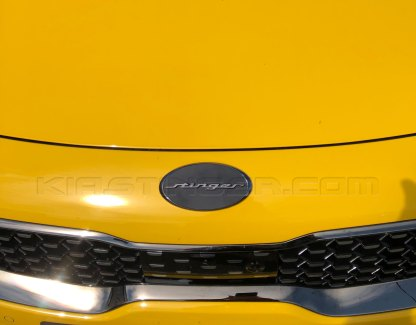 oval stinger emblem in black chrome gunmetal with black background on yellow kia stinger