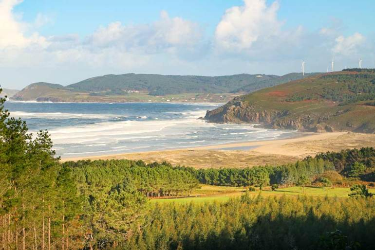 A view of the wild beach surrounded by the hills from the Camino route