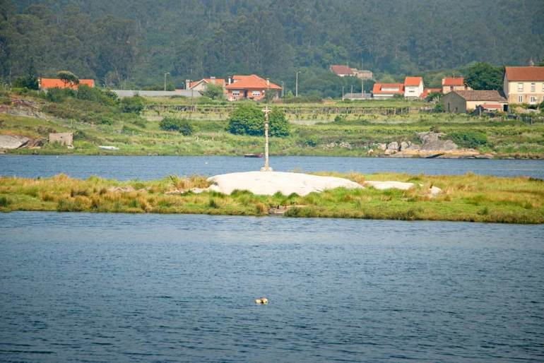 A stone cross on the big rock in the middle of the river on the Spiritual route of the Camino Portuguese
