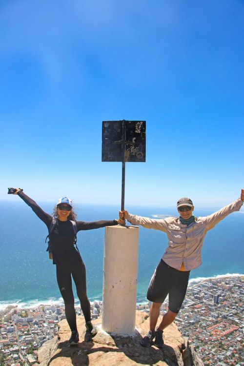 Stingy Nomads standing next to the sign marking the top of Lion's Head in Cape Town