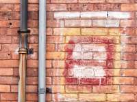 Brick Wall Spray Painted With Graffiti And Steel Pipes