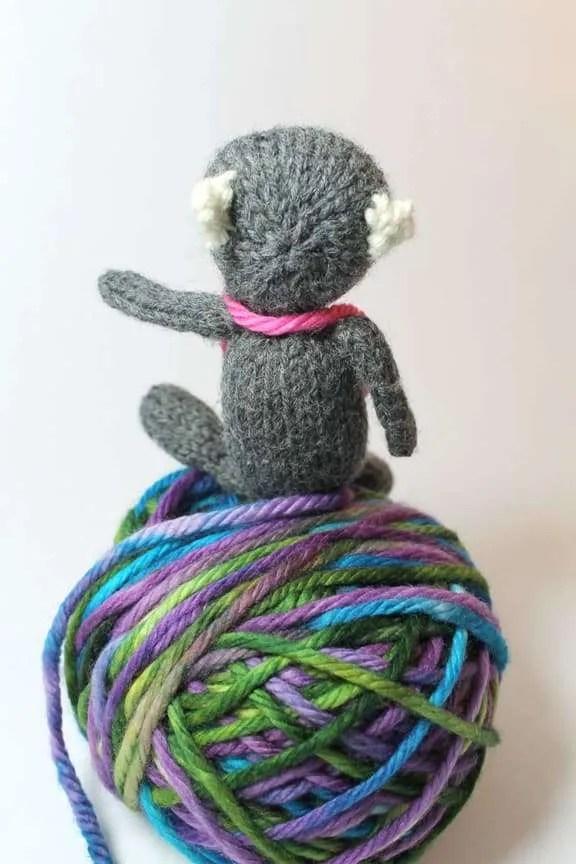 back of a little bear sitting on a ball of yarn