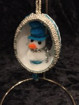 Turquoise painted egg with bead and cord embellishments. Cutouts and snowman insert.