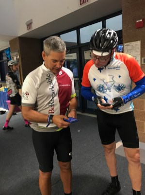 Rob Casalou shows a fellow rider how to tag all social media posts with #sjJoinMe
