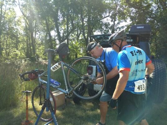 So thankful for bike mechanics. Patrick fixes Nick Graham's bike so he can keep on riding.