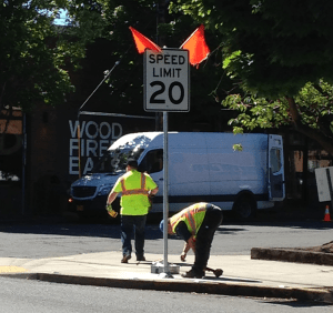 20-mph speed limit sign being installed